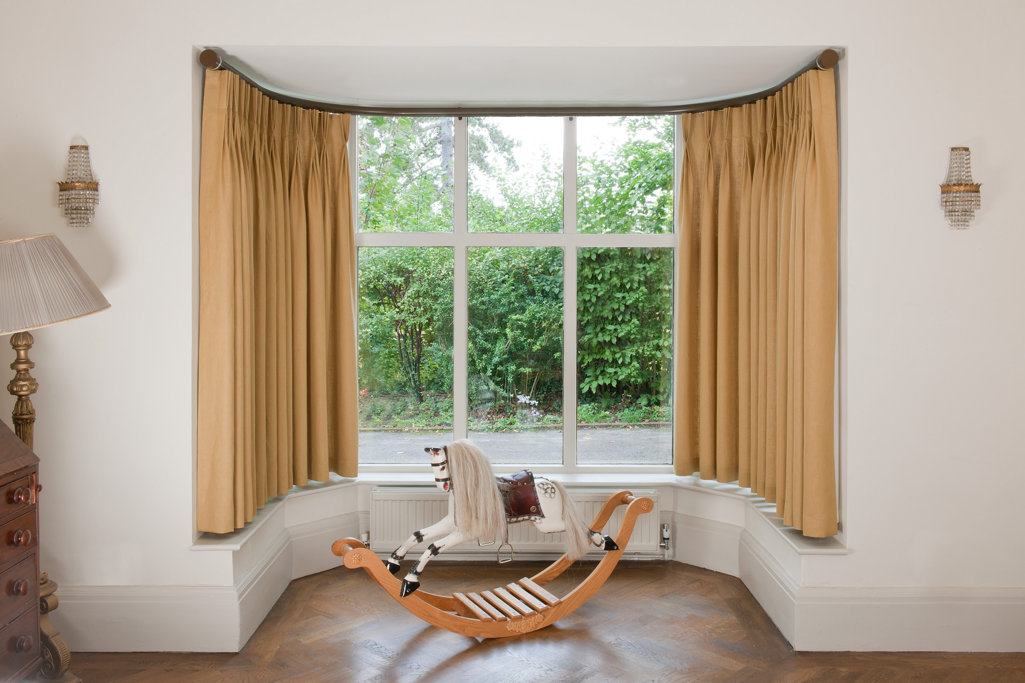 Bay curtain pole with curtains hanging